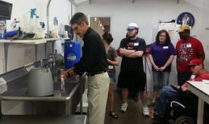 Jim from University Extension demonstrates proper handwashing techniques in a cooking class.